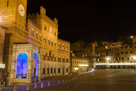 Night view of Campo Square (Piazza del Campo), Siena Palazzo Pubblico and Mangia Tower (Torre del Mangia) in Siena, Tuscany, Italy. Reklamní fotografie