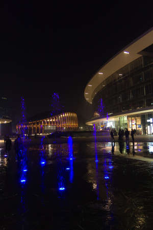 MILAN, ITALY-OCTOBER 30, 2016: Financial district night view. Illuminated water fountains. Modern skyscrapers in Gae Aulenti square. Unicredit bank tower