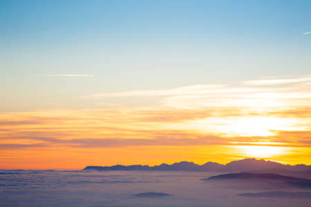 Mountain silhouette at sundown from Italian Alps. Clouds background