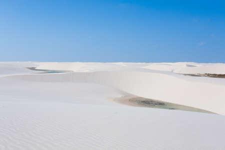White sand dunes panorama from Lencois Maranhenses National Park, Brazil. Rainwater lagoon. Brazilian landscape