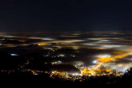 Plain illuminated partially covered by fog, soft lights.  Mount Grappa, Italian landscape Archivio Fotografico