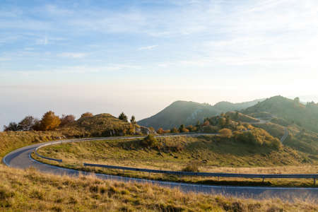 Autumn mountain landscape. Tarmac road in perspective. Grappa mountain, Italian Alps