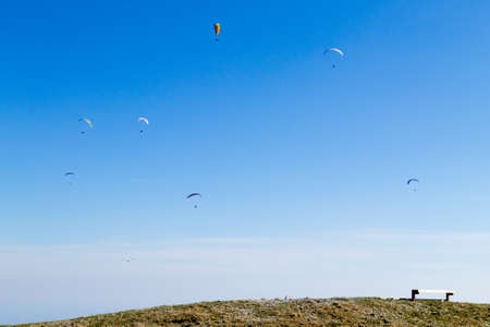 Paraglider on blue sky with empty bench on foreground. Borso del Grappa, famous paragliding site, Italy