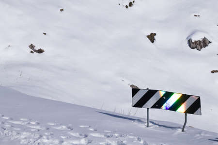 Reflections on traffic sign. Mountain road covered by snow Archivio Fotografico