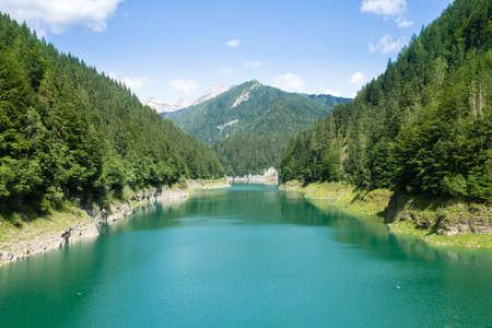 Val Noana artificial lake, Mezzano, Italy. Mountain landscape. Green water lake Archivio Fotografico