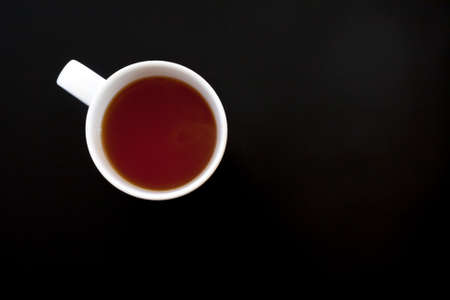 Cup of tea on black table, top view. Food background