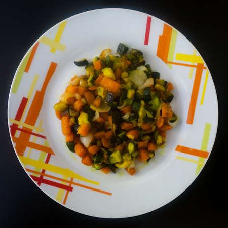 Cooked vegetables on decorated plate top view. Food background