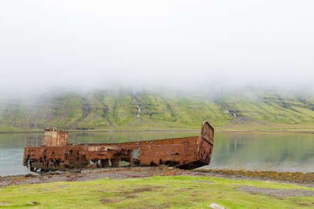 Shipwreck from Mjoifjordur fiord, east Iceland.  Icelandic view Archivio Fotografico - 146790883