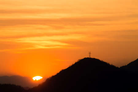Outline of mountains at sunset with electric pylon. Mountain landscape