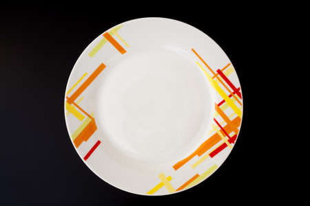 Empty decorated plate on black wooden table. Kitchen tools top view