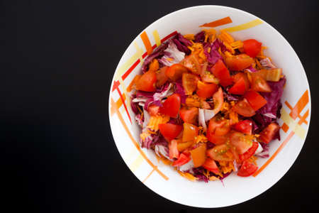 Salad with carrots and tomatoes on black table, top view. Food background