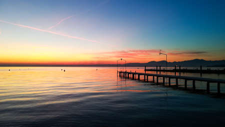 Sunset at Garda lake, Italy. Italian landscape. Pier in perspective