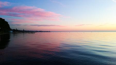 Sunset at Garda lake, Italy. Italian landscape. Pier in perspective 免版税图像