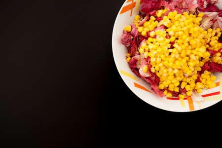 Salad with corn on black table, top view. Food background