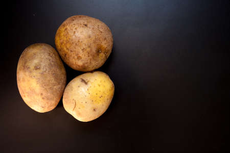 Potatoes on black table, food background. Isolated potatoes