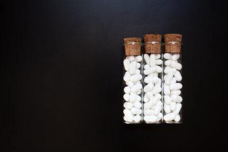 Jordan almonds in glass tube. Wedding decoration on black background