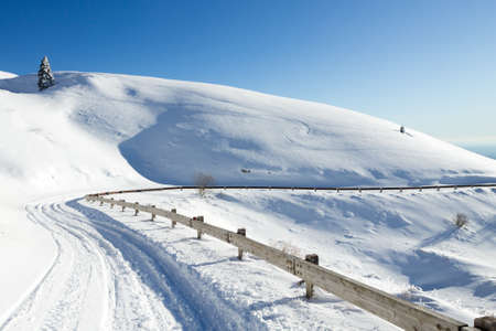 Winter landscape, curves road with snow. Mount Grappa landscape, Italy 免版税图像