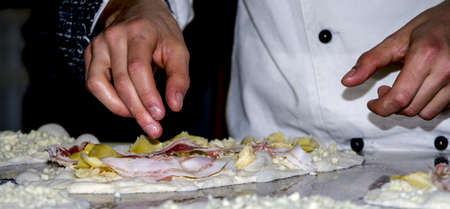 Preparing pizzas with mozzarella, bacon and artichokes for cooking photo