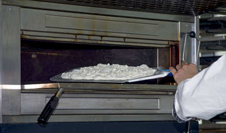 Cooking pizza dough in shovel with electric oven photo
