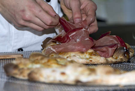 Whites pizzas cooked and stuffed with bacon, artichokes,ham and mozzarella cheese photo