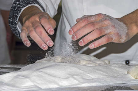Handling, working and cooking pizza dough with shovel photo