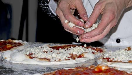 Preparing pizzas with mozzarella, bacon and artichokes for cooking photo