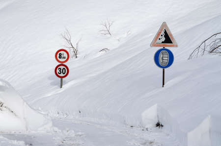 partially: Road sign on a mountain road partially covered by the snow