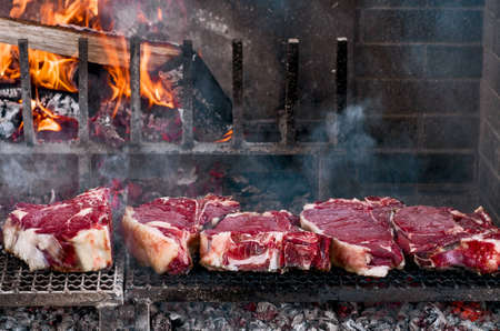 boned: Thick slices of meat from chianina cow grilling over the embers Stock Photo