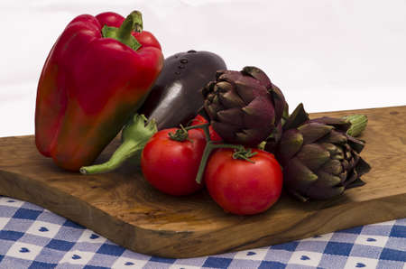 egg plant: Multicoloured fresh vegetables with artichoke, egg plant and tomato over a wooden chopping board