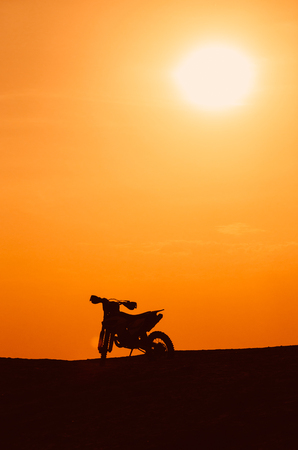 Dark silhouette of a motobike and the sun in the evening.