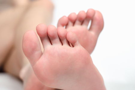 Feet of a young woman on white background close up Standard-Bild