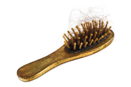 Old golden comb with hairs isolated on the white background. Problem of losing hairs 免版税图像