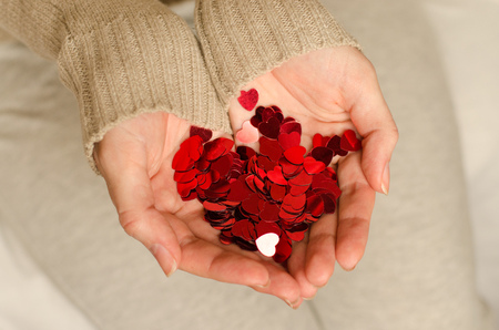 Hands of a young caucasian girl hold small hearts close up. Love and happiness are in our own hands Stock Photo