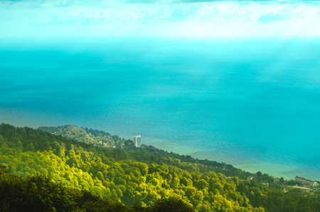 Seaside resort on green hills near azure sea top view. Seascape from above