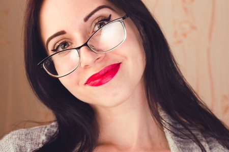 Young caucasian pretty brunette girl with glasses and red lips smiles