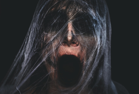 Screaming creepy character covered with spiderweb on black background. Halloween spooky creature portrait with copy space Stock Photo
