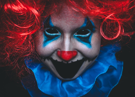 Creepy clown close up spooky halloween portrait on black background