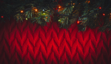 A Chrismas tree branch with glowing garland on red knitted background. Festive greeting card with copy space