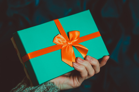 Young woman holds a gift box with a bow on dark blue background close up festive background