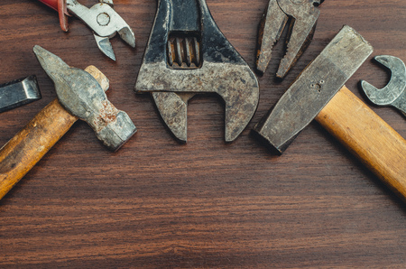 Top view layout of different tools as hammer, screwdriver, spanner and pliers on wooden background with copy space