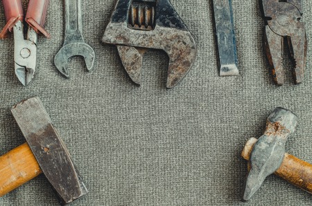 Top view different tools as hammer, screwdriver, spanner and pliers on textile background with copy space 免版税图像