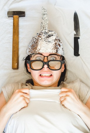 Scared paranoid woman wears foil helmet and sleeps with weapon and different glasses because of mental disorder. Concept of fears of aliens fbi or radiation