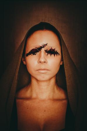Aterrador retrato de una mujer joven sin ojos con capa en la cabeza sobre fondo oscuro