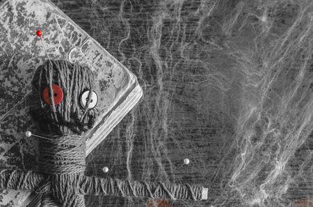 Muñeco vudú con agujas y libro antiguo sobre fondo de madera cubierto con telaraña. Copia espacio