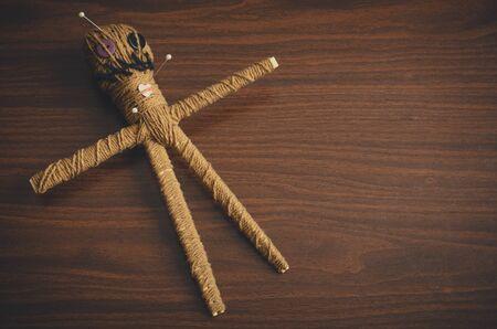 Muñeco vudú con agujas sobre fondo de madera marrón y copie el espacio. Viejo muñeco oculto para rituales espeluznantes Foto de archivo