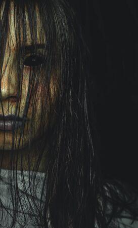 Fille maudite effrayante aux yeux noirs sur l'espace de copie de fond sombre. Affiche pour un film d'horreur Banque d'images