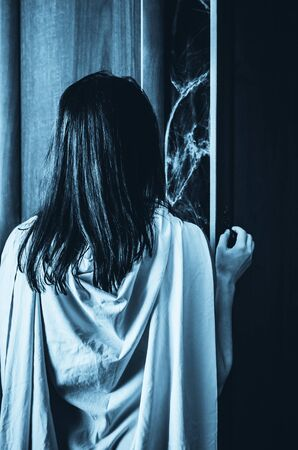 Young woman opens doors of a wardrobe with something creepy inside. Vertical poster for a horror movie