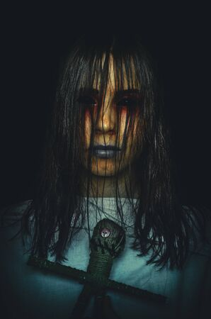 Gruselige Hexe mit Voodoo-Puppe und dunklen Augen auf schwarzem Hintergrund. Gruseliger Halloween-Charakter Standard-Bild