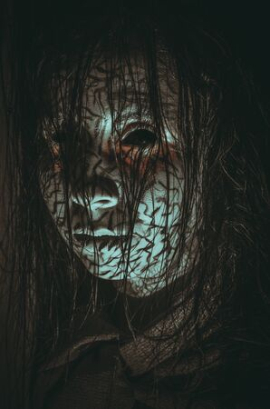 Creepy demonic girl with black eyes and cracked skin close-up portrait on dark background Reklamní fotografie