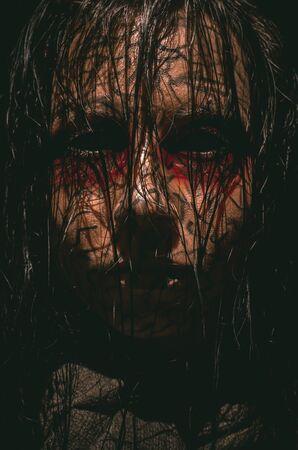 Chica infernal espeluznante con ojos negros y retrato de primer plano de piel agrietada sobre fondo oscuro Foto de archivo